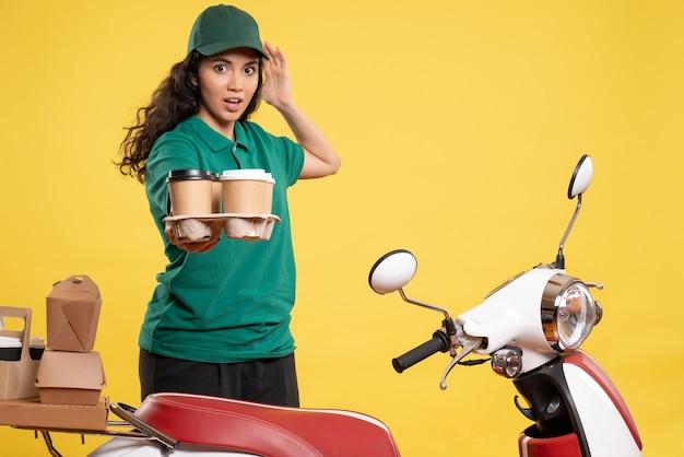 Vue de face coursier féminin en uniforme vert avec du café sur fond jaune service travailleur livraison travail nourriture femme couleur