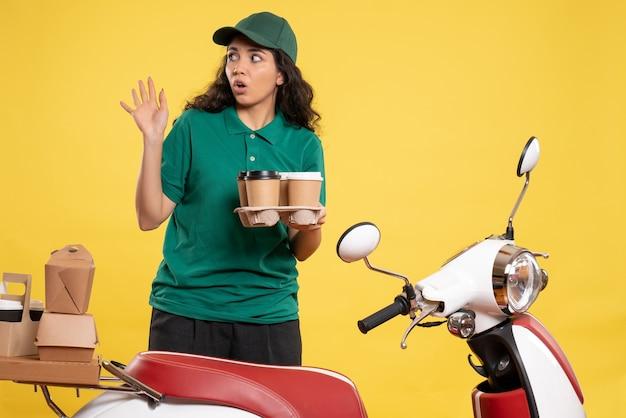 Vue de face coursier féminin en uniforme vert avec du café sur fond jaune travailleur de service livraison de travail travail alimentaire femme