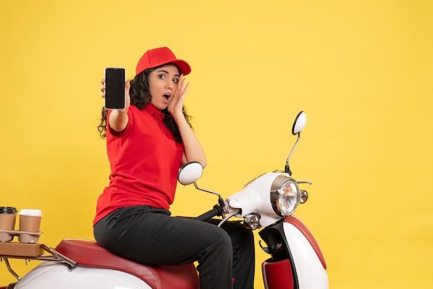 Vue de face coursier féminin à vélo pour la livraison de café tenant un téléphone sur fond jaune service de livraison uniforme travailleur travail femme