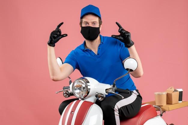 Vue de face coursier masculin en uniforme bleu et masque sur la livraison de travail rose service de restauration rapide travail à vélo covid- virus alimentaire