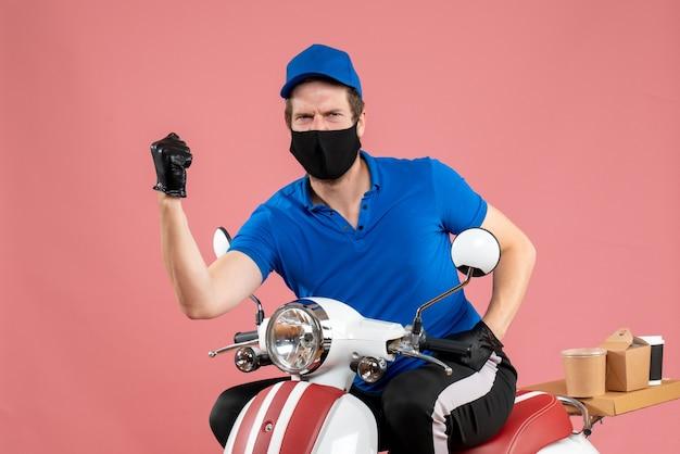 Vue de face coursier masculin en uniforme bleu et masque sur livraison de travail rose travail de vélo de restauration rapide service de virus alimentaire covid