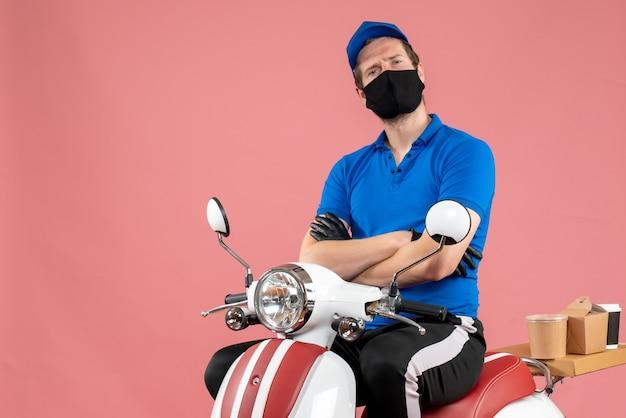 Vue de face coursier masculin en uniforme bleu et masque sur le travail de livraison de travail de vélo de virus rose travail de restauration rapide