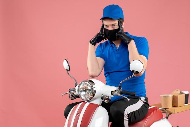Vue de face coursier masculin en uniforme bleu et masque sur un travail de livraison de travail à vélo à virus rose travail de service de restauration rapide covid