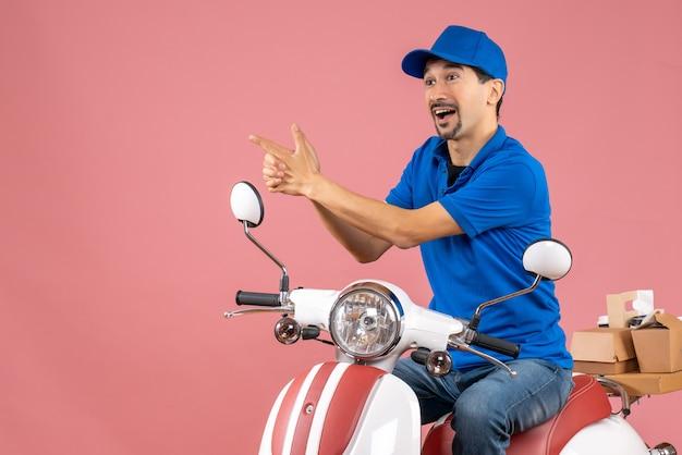 Vue de face d'un coursier souriant portant un chapeau assis sur un scooter et faisant un geste de pistolet sur fond de pêche pastel