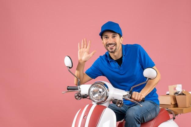 Vue de face d'un coursier souriant portant un chapeau assis sur un scooter montrant cinq sur fond de pêche pastel