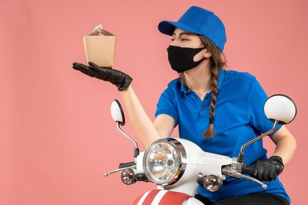 Vue de face d'une coursière portant un masque médical noir et des gants tenant une petite boîte sur fond pêche