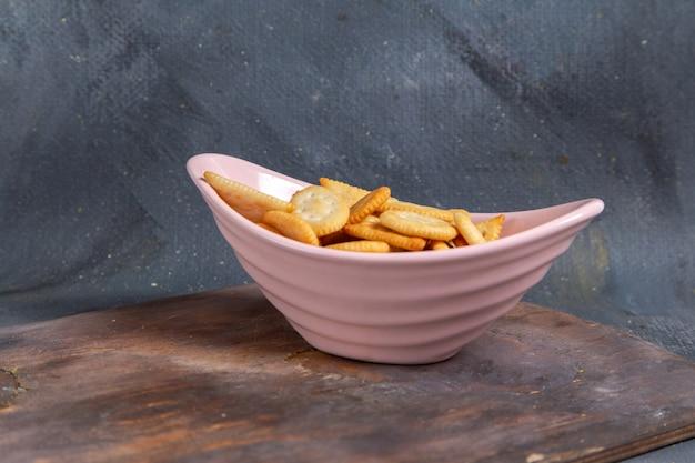 Vue de face des craquelins et chips savoureuses chips salées à l'intérieur de la plaque rose