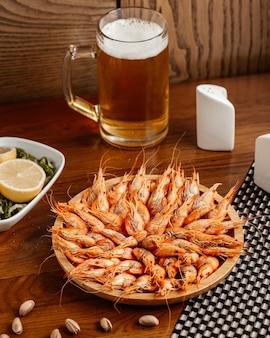 Une vue de face des crevettes fraîches avec des noix de citron et de la bière sur le repas de collation de bureau brun