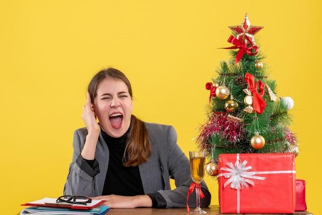 Vue de face a crié fille assise au bureau arbre de noël et cadeaux cocktail