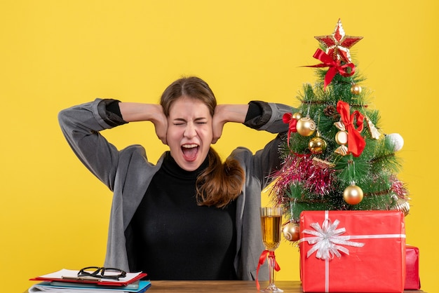 Vue de face a crié fille assise au bureau couvrant les oreilles avec ses mains arbre de noël et cadeaux cocktail
