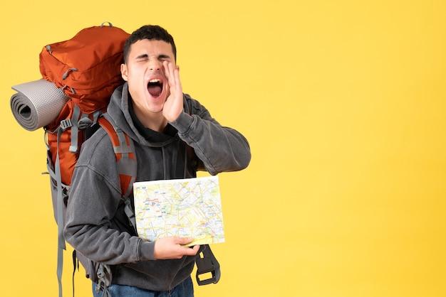 Vue de face a crié homme voyageur avec sac à dos tenant la carte