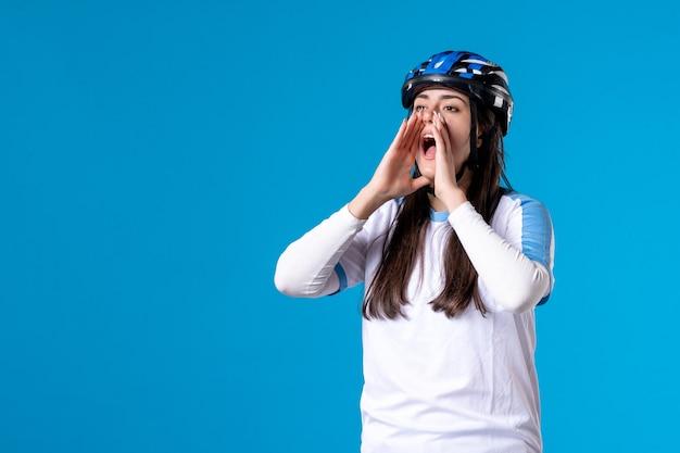 Vue de face crier jeune femme en vêtements de sport avec casque sur bleu