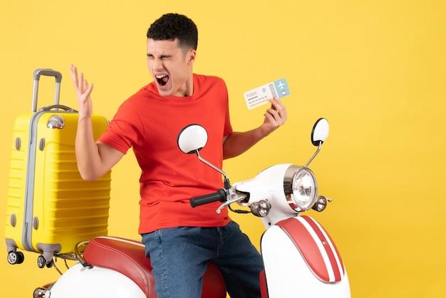 Vue de face crier jeune homme dans des vêtements décontractés sur un billet de tenue de cyclomoteur