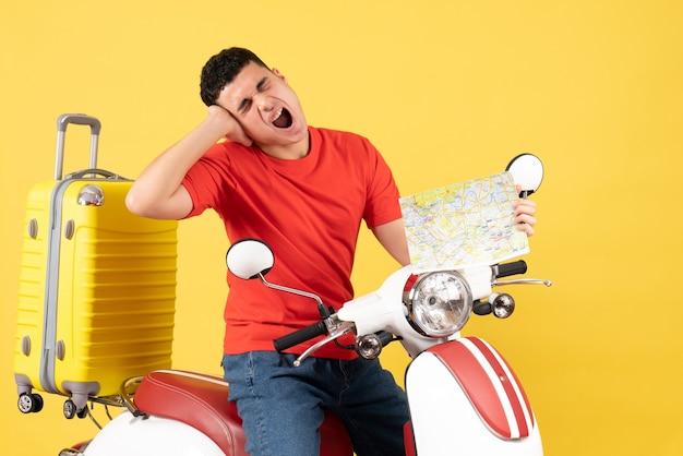 Vue de face crier jeune homme dans des vêtements décontractés sur un cyclomoteur tenant une carte de voyage
