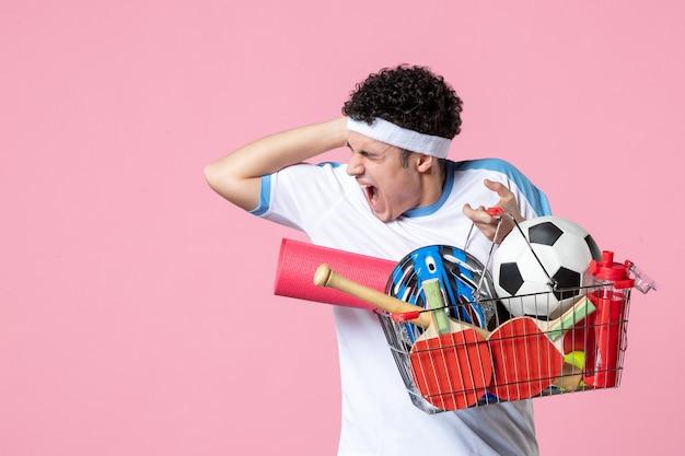 Vue de face crier jeune homme en vêtements de sport avec panier plein de choses sportives