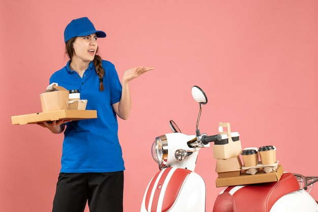 Vue de face d'une dame de messagerie confuse debout à côté d'une moto tenant du café et de petits gâteaux sur fond de couleur pêche pastel