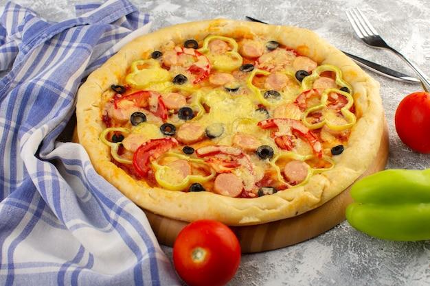 Vue de face d'une délicieuse pizza au fromage avec des saucisses aux olives et des tomates sur le bureau gris