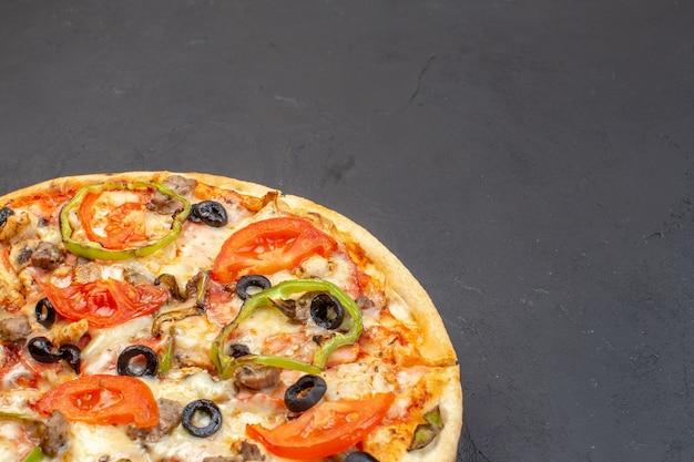 Vue de face, une délicieuse pizza au fromage se compose d'olives, de poivron et de tomates sur une surface sombre