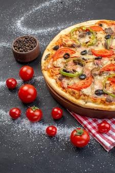 Vue de face délicieuse pizza au fromage avec des tomates rouges sur une surface sombre