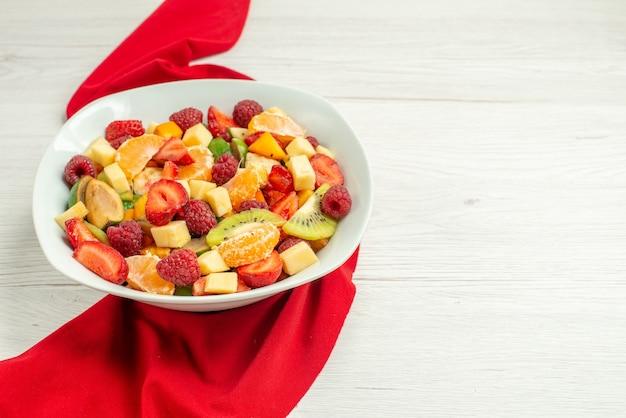Vue de face délicieuse salade de fruits avec du tissu rouge sur une surface blanche agrumes exotiques baies fruitées mûres photo moelleuse