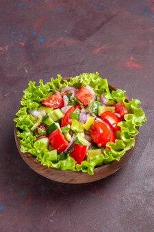 Vue de face délicieuse salade de légumes en tranches avec des ingrédients frais sur un espace sombre