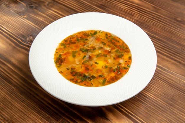 Vue de face délicieuse soupe aux légumes avec des verts sur table en bois brun soupe repas de légumes assaisonnement alimentaire