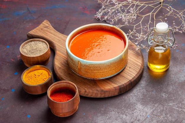 Vue de face délicieuse soupe aux tomates avec assaisonnements sur un espace sombre