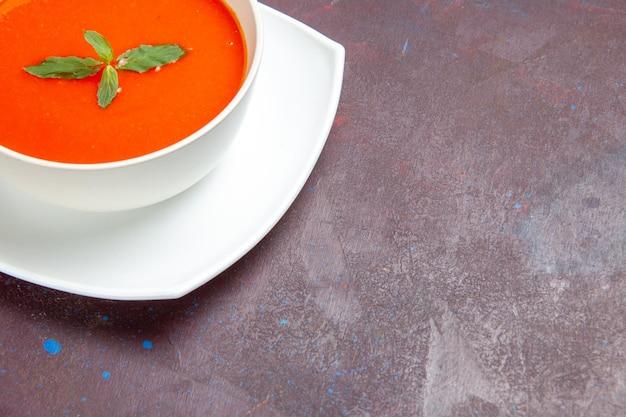 Vue de face délicieuse soupe aux tomates plat savoureux avec une seule feuille à l'intérieur de la plaque sur un espace sombre