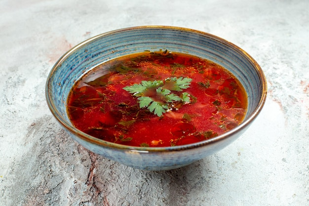 Vue de face délicieuse soupe de betterave ukrainienne célèbre de bortsch avec de la viande à l'intérieur de la plaque sur un espace blanc