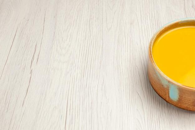 Vue de face délicieuse soupe à la crème soupe de couleur jaune sur un bureau blanc soupe sauce repas plat à la crème dîner