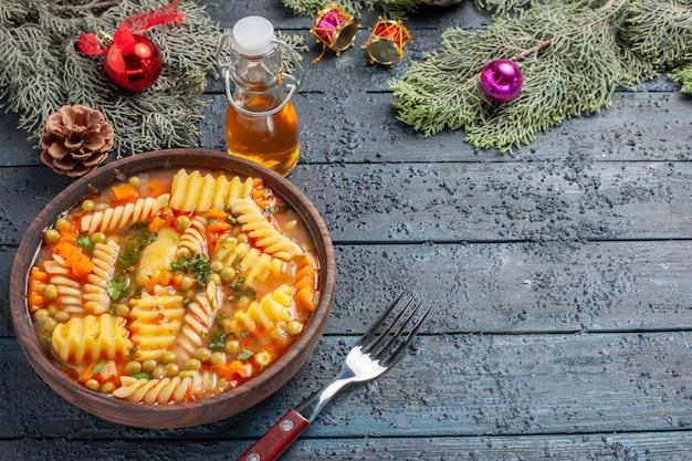Vue de face délicieuse soupe de pâtes à partir de pâtes italiennes en spirale avec des verts sur un bureau bleu foncé cuisine plat de soupe de pâtes couleur du dîner
