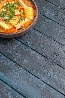 Vue de face délicieuse soupe de pâtes à partir de pâtes italiennes en spirale avec des verts sur le plat de bureau sombre soupe de pâtes italiennes sauce dîner