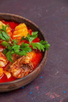 Vue de face délicieuse soupe de sauce à la viande avec des légumes verts et des pommes de terre tranchées sur une surface sombre soupe de soupe repas de nourriture dîner