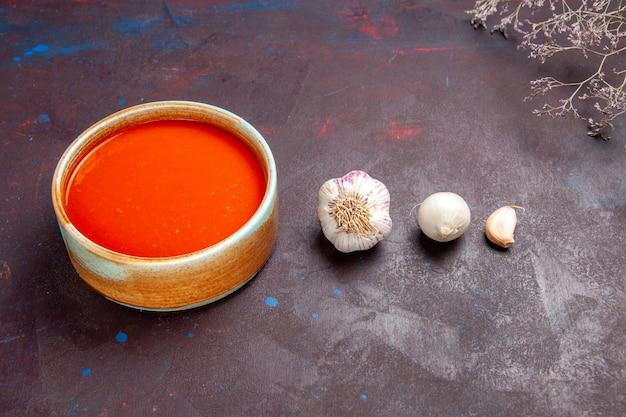 Vue de face délicieuse soupe de tomates cuite à partir de tomates fraîches sur un espace sombre