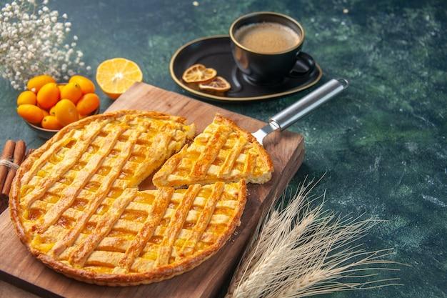 Vue de face délicieuse tarte kumquat avec un morceau en tranches et tasse de café sur fond sombre