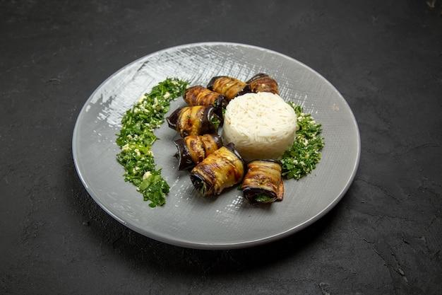 Vue de face de délicieuses aubergines cuites avec des légumes verts et du riz sur une surface sombre dîner alimentaire huile de cuisson repas de riz