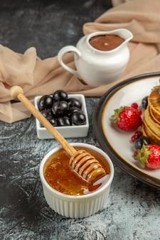 Vue de face de délicieuses crêpes aux fruits et miel sur une surface légère gâteau aux fruits sucré