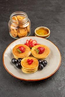 Vue de face de délicieuses crêpes aux fruits sur la surface sombre de la tarte aux fruits gâteau sucré