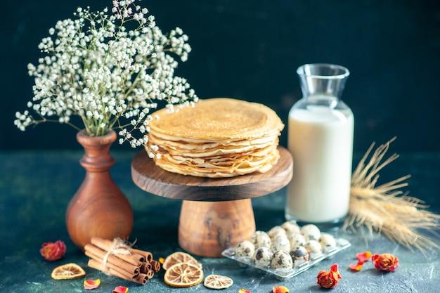 Vue de face de délicieuses crêpes sur un bureau en bois et une tarte au gâteau de petit-déjeuner sombre au miel, au thé du matin, au lait de dessert