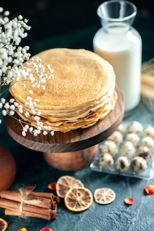 Vue de face de délicieuses crêpes sur un bureau en bois et tarte au gâteau de petit-déjeuner sombre dessert au thé au miel sucré lait