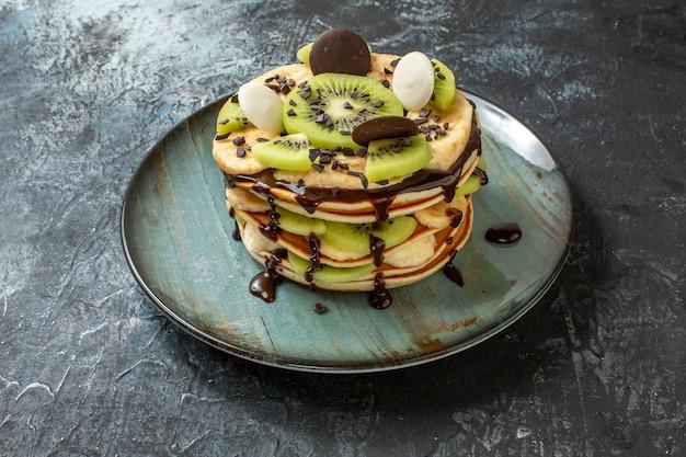 Vue de face de délicieuses crêpes avec des fruits tranchés et du chocolat sur une surface gris foncé