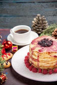 Vue de face de délicieuses crêpes à la gelée avec des fraises et une tasse de thé sur un espace sombre