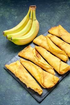 Vue de face de délicieuses crêpes roulées avec des bananes sur une surface sombre