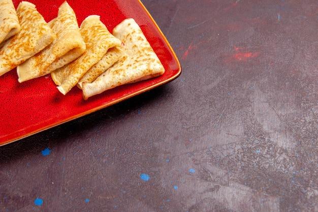 Vue de face de délicieuses crêpes sucrées à l'intérieur d'une assiette rouge sur un espace sombre