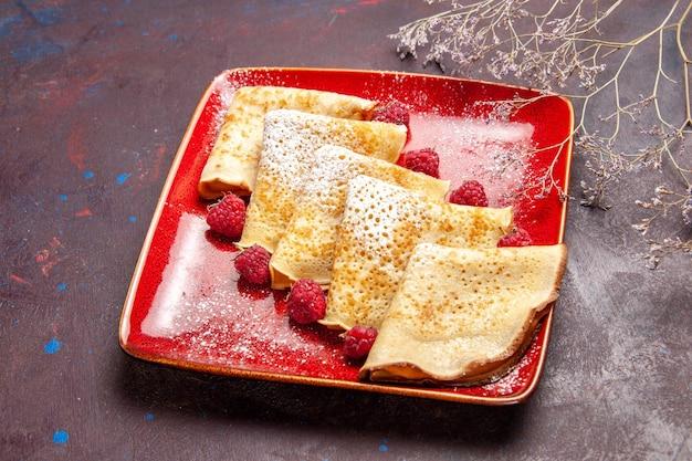 Vue de face de délicieuses crêpes sucrées à l'intérieur d'une assiette rouge avec des framboises sur un espace sombre