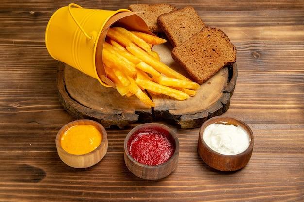 Vue de face de délicieuses frites avec des assaisonnements sur un repas de pain de fast-food de pomme de terre de bureau brun