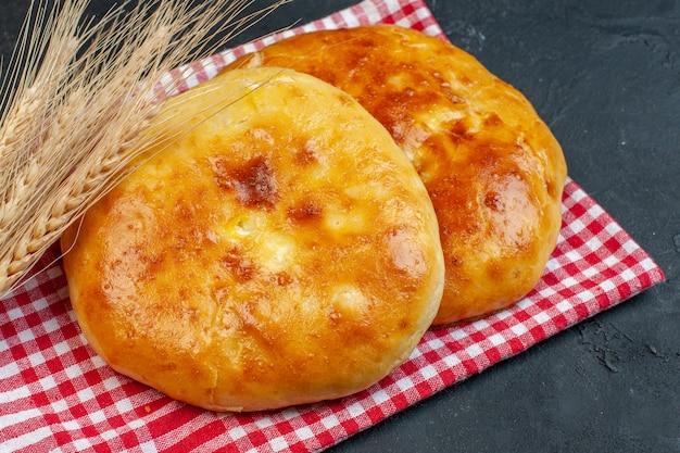 Vue de face de délicieuses pâtisseries fraîches cuites au four sur une serviette dénudée rouge et une pointe sur un fond noir foncé