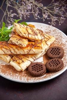 Vue de face de délicieuses pâtisseries sucrées avec des biscuits au chocolat sur un espace sombre