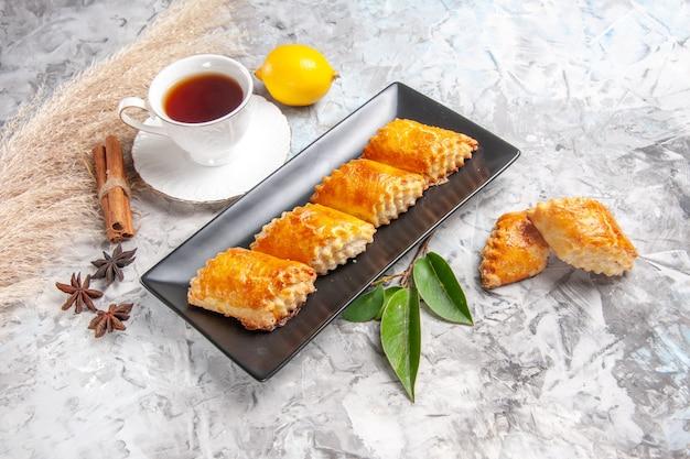 Vue de face de délicieuses pâtisseries sucrées avec du thé sur une table blanche pâtisserie à tarte sucrée
