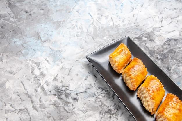 Vue de face de délicieuses pâtisseries sucrées à l'intérieur d'un moule à gâteau sur un gâteau sucré de pâtisserie à tarte de table blanche